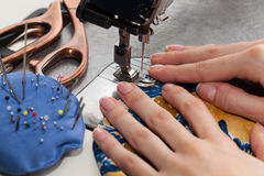 Sewing a dress. Woman's hands with dress at sewing machine royalty free stock photography