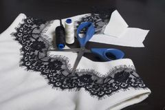 Sewing and dressing. On the dark surface is a white dress with a black ribbon sewn for decoration. Nearby lie scissors, thread ree. Ls and trimming materials of Royalty Free Stock Photo
