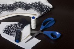 Sewing and dressing. On the dark surface is a white dress with a black ribbon sewn for decoration. Nearby lie scissors, thread ree. Ls and trimming materials of Royalty Free Stock Image