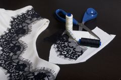Sewing and dressing. On the dark surface is a white dress with a black ribbon sewn for decoration. Nearby lie scissors, thread ree. Ls and trimming materials of Royalty Free Stock Images