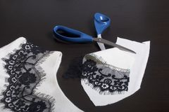 Sewing and dressing. On the dark surface is a white dress with a black ribbon sewn for decoration. Nearby there are scissors and s. Craps of materials of the Royalty Free Stock Images