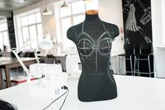 Sewing Dummy in  Atelier Interior. Interior of modern atelier workshop with sewing dummy on table in foreground, no people, copy space background Stock Images