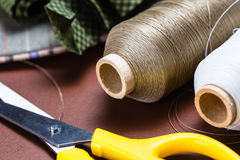 Sewing equipment. Closeup thread spools on sewing desk Stock Photography
