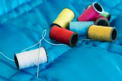 Sewing Equipment. Needle and thread sitting on a blue quilt Royalty Free Stock Images