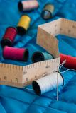 Sewing Equipment. Needle and thread sitting on a blue quilt Royalty Free Stock Photography