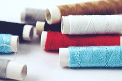 Sewing equipment. Roll of color thread close up on white background Stock Images