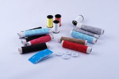 Sewing equipment. Roll of color threads, needle, measuring tape and white Stock Photos
