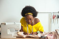 Sewing fabric with needle at seamstress workplace. African female sewing fabric with needle at seamstress workplace royalty free stock images
