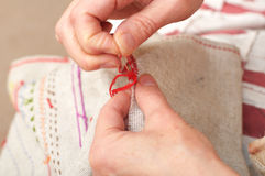 Sewing with floss needle and thread Royalty Free Stock Photo