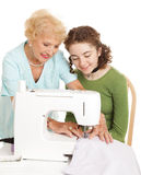 Sewing With Grandma. Senior woman showing her teen granddaughter how to use a sewing machine. White background