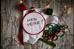 Sewing by hand in white taffeta NEW YEAR 2019 with red and green threads royalty free stock photo
