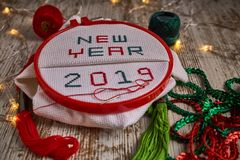 Sewing by hand in white taffeta NEW YEAR 2019 with red and green threads stock images