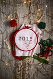Sewing by hand in white taffeta NEW YEAR 2019 with red and green threads royalty free stock photos