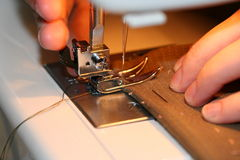 Sewing hands. Hands work a sewing machine Royalty Free Stock Photography