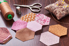 Sewing of hexagon pieces of fabric a quilt Grandmother`s Flower Garden stock photo