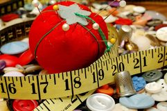 Sewing Items. Assorted colorful buttons, tape measure, and pin cushion with pins royalty free stock photos