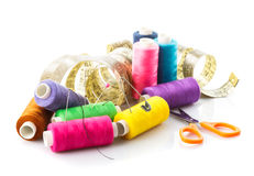 Sewing items. Multicoloured threads, pins, meter and scissors on white stock photos