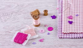 Sewing items with a check fabrics, buttons, thread and pins Royalty Free Stock Photos