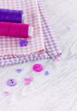 Sewing items with a check fabrics, buttons, thread and pins Royalty Free Stock Images