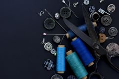 Sewing items,closeup. Top view. Flat lay. Sewing items,closeup. Scissors,threads, needles and buttons on black background. Top view. Flat lay. Text space stock photography
