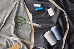 Sewing Items on Fabric. Closeup image of different sewing items on grey fabric: scissors, measuring tape and sewing spools stock images