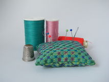 Sewing Items on white background. Colorful Sewing Items (pincushion, yarn, needle, pins and thimble Royalty Free Stock Photos