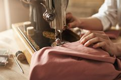 Sewing keeps my mind relaxed. Cropped shot of female tailor working on new project, making clothes with sewing machine. In workshop, being busy. Young designer royalty free stock photography