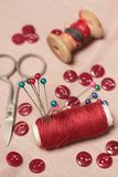 Sewing kit. Bobbins, scissors, buttons and pins. Focus is on the red bobbin with pins Royalty Free Stock Images