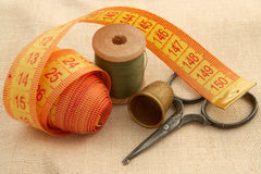 Sewing kit  on canvas. Сollection of sewing tools and supplies in a sewing kit on unbleached linen. Items include khaki thread, needle, tape measure, ancient Royalty Free Stock Image