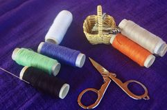 Sewing kit. Sewing cotton on purple fabric Stock Photo