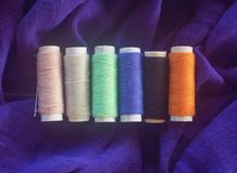 Sewing kit. Sewing cotton on purple fabric Stock Photography