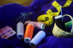 Sewing kit. Sewing cotton on purple fabric Stock Photos