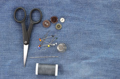 Sewing kit on jeans background, copy space. Royalty Free Stock Photo