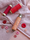 Sewing kit in pink on cloth background Stock Images