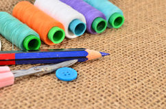 Sewing kit. Scissors, bobbins with thread and needles on the old Royalty Free Stock Image