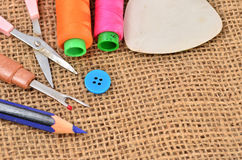 Sewing kit. Scissors, bobbins with thread and needles on the old Stock Images