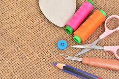 Sewing kit. Scissors, bobbins with thread and needles on the old Royalty Free Stock Images