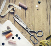 Sewing kit. Scissors, bobbins with thread and needles on the old wooden background Stock Image