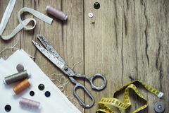 Sewing kit. Scissors, bobbins with thread and needles on the old wooden background Royalty Free Stock Image