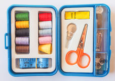 Sewing kit. Travel sewing kit including thread spools, scissors, needles, measuring tape, buttons and thimble Stock Image