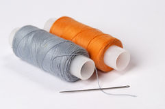 Sewing kit. Two coils of thread grey and orange with needle over white background Stock Images