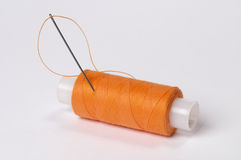 Sewing kit. Two coils of thread grey and orange with needle over white background Stock Photo