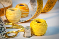 Sewing kit in yellow. Close-up on sewing kit with scissors, thimble, needle, thread and tape measure. Accent colour: yellow Royalty Free Stock Photos