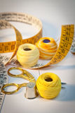 Sewing kit in yellow, portrait. Close-up on sewing kit with scissors, thimble, needle, thread and tape measure. Accent colour: yellow. Portrait orientation Stock Images