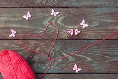 Sewing and knitting. Knitting on a wooden background. Buttons in the form of hearts and butterflies. Stock Images