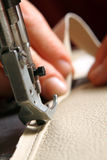 Sewing machine. In action for working leather for a sofa stock images