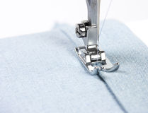 Sewing machine and blue fabric. Closeup of sewing machine and blue fabric Stock Photo