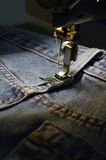 Sewing machine and blue jeans. Textile industry concept Royalty Free Stock Photography