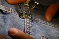 Sewing machine and blue jeans. Close up of hands using sewing machine, textile industry concept Royalty Free Stock Photos