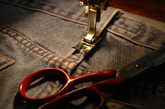 Sewing machine and blue jeans Royalty Free Stock Photography